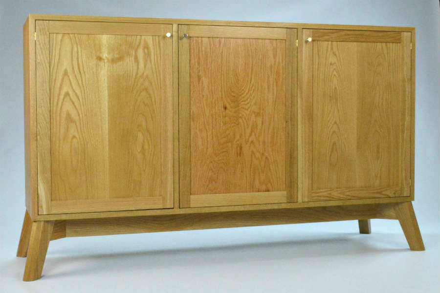 Intersection Cabinet. White Oak Cabinet with Book Matched Panel Doors. Hand cut Dovetails carcass for strength. The angle legs give a strong stable base. The line is offered as a sideboard/buffet, low and tall media consoles, storage consoles, and small sideboard. Custom made timber furniture. Custom made furniture and furniture maker.