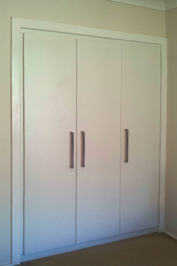 Made to replace an old wardrobe in white stain poly paint and large stainless-steel handles. It gives a modern contemporary feel to what was an old-style bedroom. custom made joinery and cabinet making