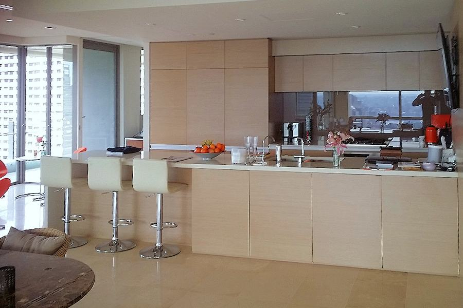 Custom made kitchen in Hyde park. Made from New Age Navurban Oak Veneer with integrated appliances. With Blum push touch draws and doors give this kitchen a clean and modem look. The stone bench top with breakfast bar and water fall edge. Custom made joinery and cabinet making.