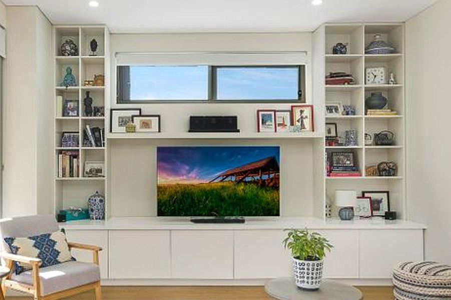 Custom made Entertainment unit with free floated shelf and bookcase each side. This unit has solf close push touch doors and finshed in white satin ploy. Custom made joinery and cabinet making.